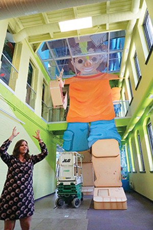 Board president Rachael Thomson is demonstrating how large Active Alex is.  Active Alex is a three-story, 40-foot-tall child that you children climb in, through and around to learn about all of the body's systems. - PHOTO BY LEE MILNER