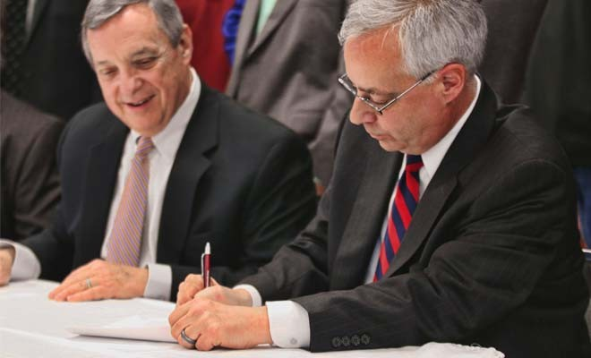 With U.S. Sen. Dick Durbin of Illinois looking on, Ken Humphreys, CEO of the FutureGen Alliance, signs a labor agreement on Monday to provide union labor for the FutureGen project planned in a rural area outside Jacksonville. The agreement may signal that - PHOTO BY PATRICK YEAGLE