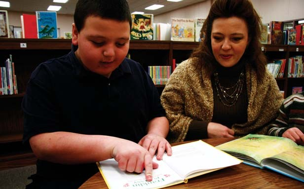 Jacob Moore and his mother, Becky, read a book in the Ball Elementary School library. - PHOTO BY PATRICK YEAGLE