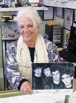 Edith Flannigan, shopkeeper at the Memories Antiques and Collectibles store on the east side of the Benton Square, poses with a signed portrait of the pre-1963 Beatles, including original drummer Pete Best. The antique store has very little in the way of - PHOTO BY WILLIAM FURRY