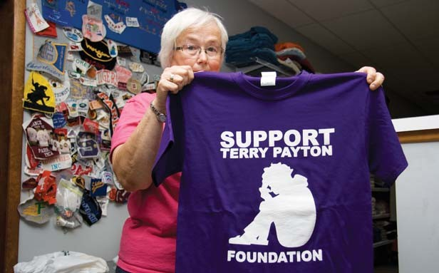 Teri Dennis, owner of Teri's Threads in Paris, holds a T-shirt sold at her shop to raise money for Terry Payton's defense fund. - PHOTO BY PATRICK YEAGLE