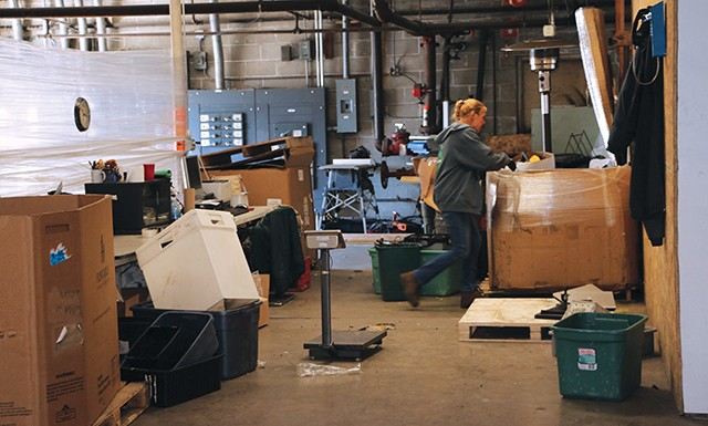 Tracy Bixler rummages through a box in BLH's special project section. Companies such as Bunn and Mercedes Benz send equipment to BLH in order to be broken down and destroyed to prevent their parts being sold on Ebay and the Grey Market for resale. - PHOTO BY BRANDON TURLEY