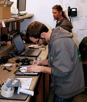 Bryan Ohl (front) and Brian Morris (back) work in the repair lab of BLH. - PHOTO BY BRANDON TURLEY