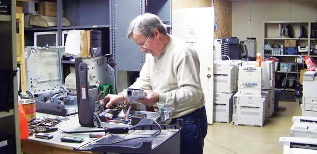 Fred Carter salvaging usable parts from a donated computer. - PHOTO BY ERICKA HINE