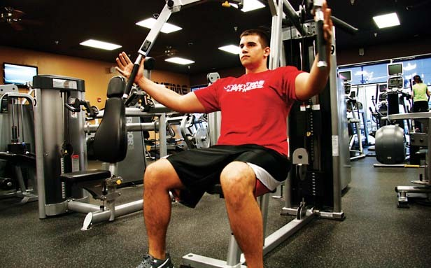 Ryan Helm, an assistant manager at Anytime Fitness, lifts his way to health. - PHOTO BY PATRICK YEAGLE