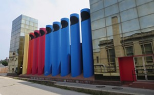 "The giant colorful ""crayons"" or ""organ pipes"" of the AT&T/SBC Switching Center compliment the mirrored glass façade of the building designed by Paul Kennon of Caudill, Rowlett, Scott in 1978. - PHOTO BY JOHN CAMPER."
