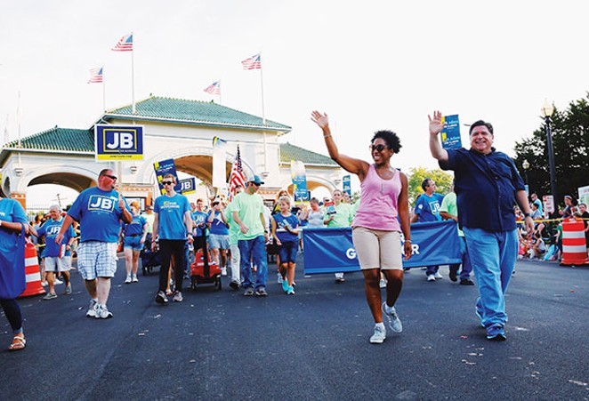 Pritzker waving to th​e crowd with running mate Rep. Julianna Stratton, D-Chicago, at the Illinois State Fair Twilight Parade in August.