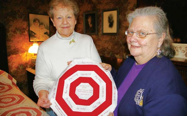 Vachel Lindsay Home State Historic Site administrator Jennie Battles, left, and Prairie Arts Chapter Embroiderer's Guild of America president Hope Wright hold a piece of the new quilt that the VLH is replicating from a 1912 quilt, shown to th - PHOTO BY ANITA STIENSTRA