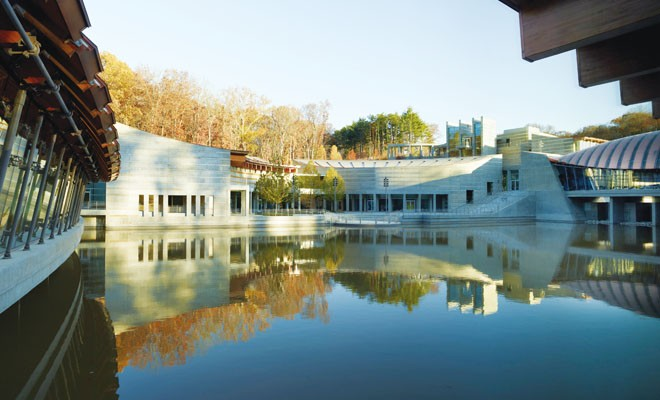 The Crystal Bridges Museum of American Art, designed by architect Moshe Safdie, is a series of pavilions nesttled in a pond.