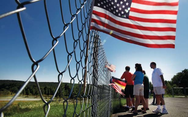 Visitors peer past the fence to the Flight 93 National Memorial, at the Flight 93 crash site and the newly completed memorial in Shanksville, Pa. - HOTO BY LAURENCE KESTERSON/MCT