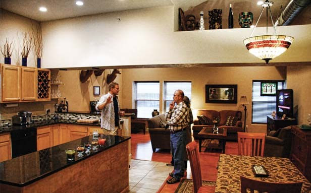 Chris Nickell of Springfield, left, shows visitors around the apartment that he and his wife renovated in the building at 118 S. 4th St. The Nickells bought the building last year and plan to finish renovating more units in the coming months. - PHOTO BY PATRICK YEAGLE