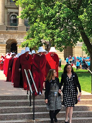 Sen. Melinda Bush, D-Grayslake, and Rep. Kelly Cassidy, D-Chicago, arrived at a rally outside the Statehouse trailed by about 60 women dressed as Handmaids, characters from Margaret Atwood's dystopian novel. - PHOTO COURTESY OF PLANNED PARENTHOOD OF ILLINOIS