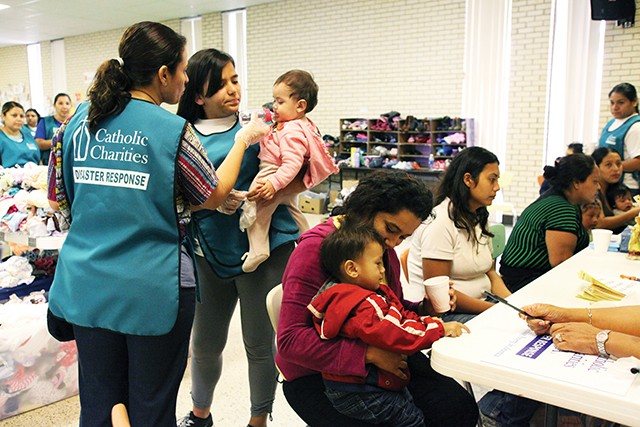Two volunteers with a Catholic Charities disaster relief team give a Central American refugee baby a bottle containing pedialyte, while a mother offers her young son a cup of water at the reception hall of Sacred Heart Catholic Church where they will rece