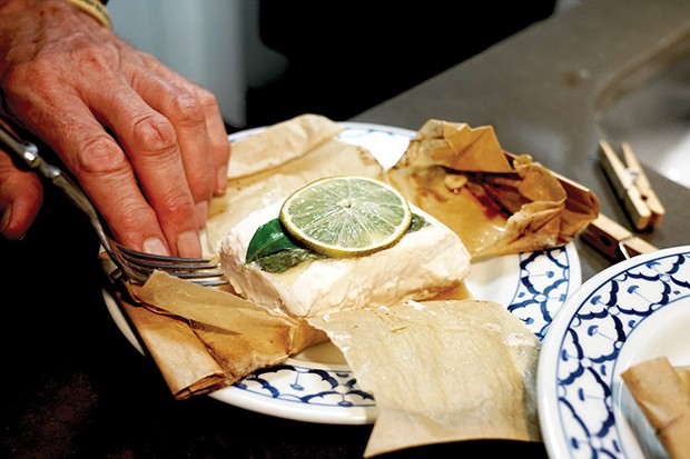 Opening the fish en papillote.
