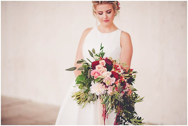 Bride Kaitlin Dietrich had a clutch bouquet with a waterfall in front. The flowers include peonies, hyperricum berries, roses, cushion mums, seeded eucalyptus, Italian ruscus and olive foliage. - PHOTO BY KARA EVANS PHOTOGRAPHY