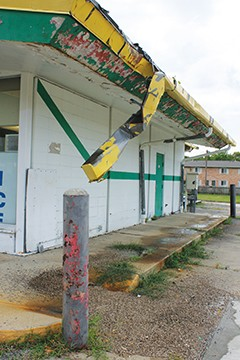 Gutter dangles from a vacant and abandoned gas station. - PHOTO BY JOE COPLEY.