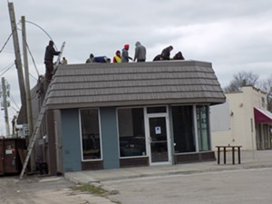 Roofers hard at work as 5 p.m. draws near. - PHOTO BY BRUCE RUSHTON