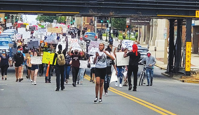 Nykeyla Henderson leads marchers through downtown Springfield. The teen says she wants more youth - programming in the city. - PHOTO BY RACHEL OTWELL.