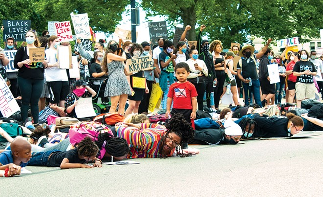 At the June 1 protest at the Capitol, Tiara Standage, center front, and three of her children lie on the pavement in solidarity with George Floyd, while her little boy looks on. - PHOTO BY BRANDON TURLEY