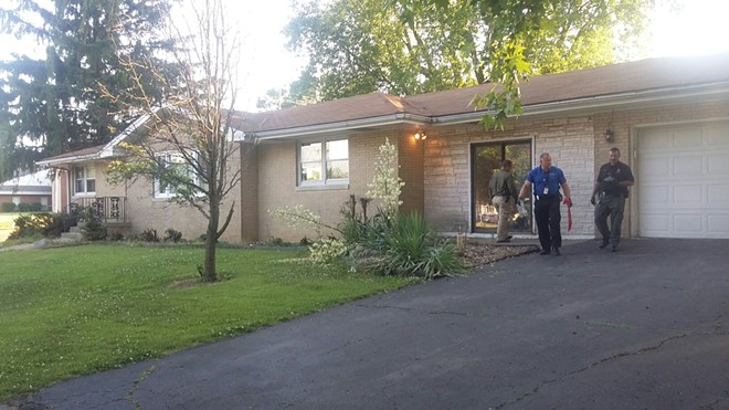 Police search a home recently acquired by Collins, not far from his Laketown house. - PHOTO BY BRUCE RUSHTON