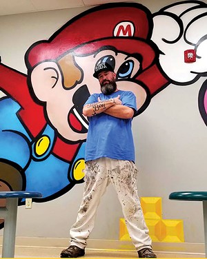 Ron stands with his completed Super Mario mural located in the cafeteria of the Lincoln Prairie Behavioral Health Center in Springfield. Spray-painted November 2019.