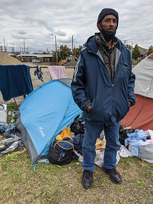 Markey Surratt outside his tent stuffed with clothes, which he says he will give to the needy. - PHOTOS BY BRUCE RUSHTON