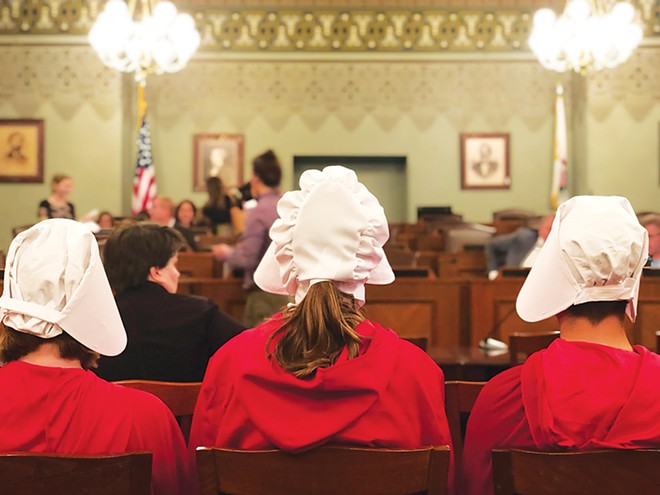 Activists dressed as handmaids observed an Illinois House human services committee meeting in May of 2019 as the Reproductive Health Act was under consideration. The Handmaid's Tale is a book by Margaret Atwood, published in 1985, about a dystopian, patriarchal society where fertile women are enslaved as breeders. The book follows the women's attempts to gain their independence. The novel was made into a popular television series on Hulu, with the first episode released in 2017. Handmaid outfits have become common for those demonstrating in support of reproductive health care in recent years. - PHOTO BY JULIE LYNN