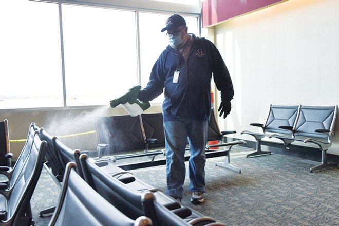 Springfield Airport Authority custodian Jim Coleman uses an electrostatic spraying machine to disinfect the waiting area at Abraham Lincoln Capital Airport. - PHOTO BY DAVID BLANCHETTE