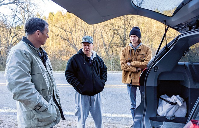 Hindi, center, discusses strategy with Greg Campbell, left, and Chad Campbell, right, near a suspected North Carolina cockfight that didn't happen. - PHOTO BY BRUCE RUSHTON