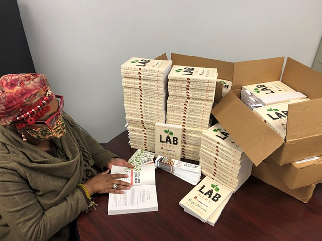 LLCC Community Education program assistant and Academy of Lifelong Learning member Jennifer Lewis. She is prepping the books to add a Big Read label inside the cover and stuffing them with an NEA Big Read bookmark. - PHOTO COURTESY OF LINCOLN LAND COMMUNITY COLLEGE.