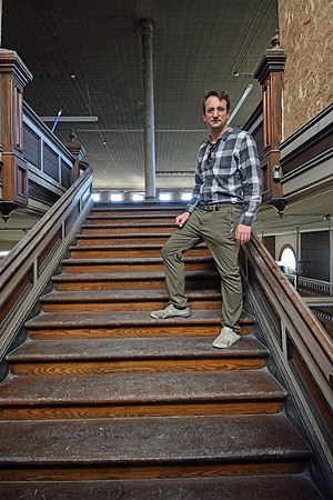 Douglas Pope on the staircase leading to the Broadgauge's second floor ballroom. - PHOTO BY DAVID BLANCHETTE