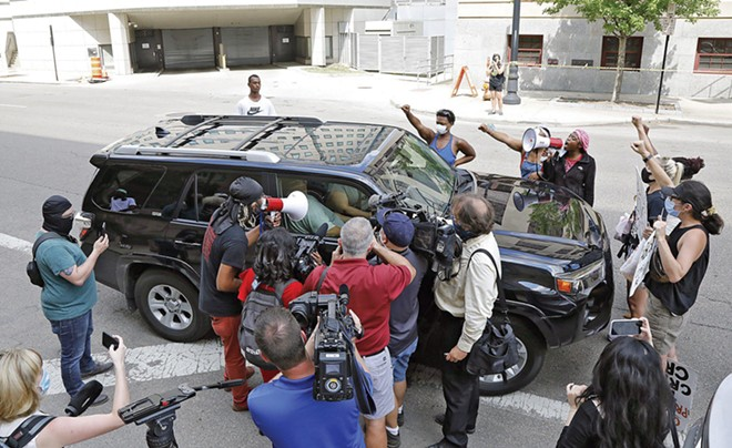 Protesters and reporters outside a federal courthouse in Ohio surround a vehicle occupied by John Householder, former speaker of the Ohio House of Representatives, who's been charged in an alleged $60 million bribery scheme to subsidize nuclear plants. Although no longer speaker, Householder was reelected last year and remains a lawmaker. - CREDIT: KYLE ROBERTSON/DISPATCH.