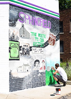 Korbin King is painting a mural on the east wall of Route History to highlight Springfield-area - landmarks that are part of Black history. - PHOTO BY NORMA ZUNIGA