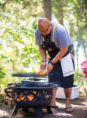 Chef Yia Vang cooking over a wood fire. - PHOTO BY LAUREN CUTSHALL
