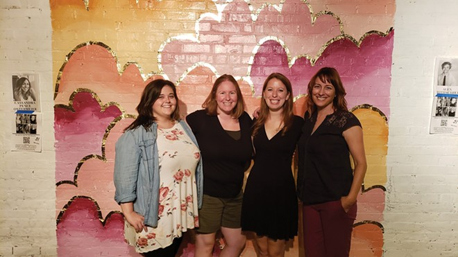 Kayla Graven, DSI executive director as of July 1, artists Corrin McWhirter and Erin Svendsen, and Lisa Clemmons Stott. DSI has worked to bring more public art - downtown through projects such as Art Alley, launched in 2017. The women stand in front of a mural by Cassandra Ostermeier. - COURTESY OF LISA CLEMMONS STOTT