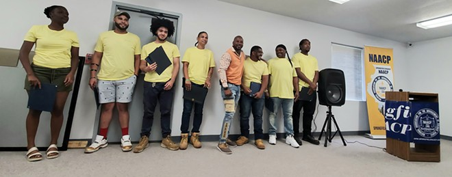 Calvin Pitts, center in orange, stands with recent graduates of his construction training program duringa ceremony at the NAACP headquarters in Springfield. - CREDIT: RACHEL OTWELL
