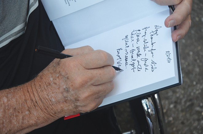 George Ryan signs a copy of his book, Until I Could Be Sure. - PHOTO BY DAVID BLANCHETTE