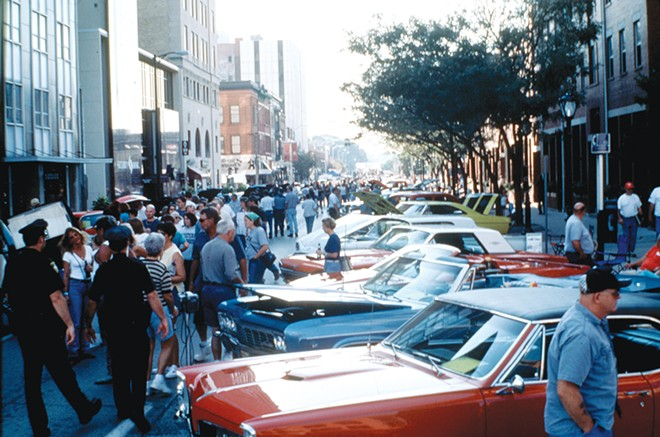 Cars and spectators fill Monroe Street from an early show. Notice the pay phone in the right side of the photo.