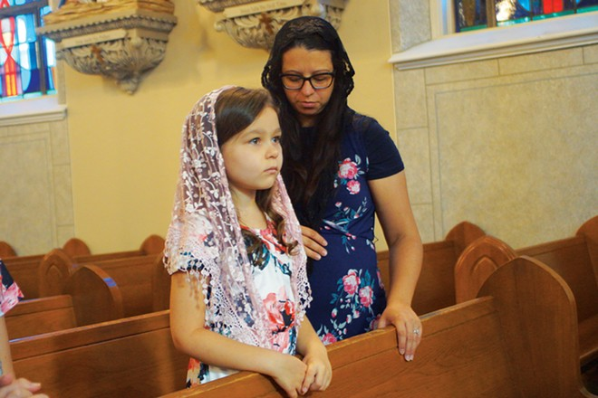 Gabi Lemmon and her 7-year-old daughter, Cecilia, wear the traditional chapel veils during a Latin Mass. - PHOTO BY SCOTT REEDER