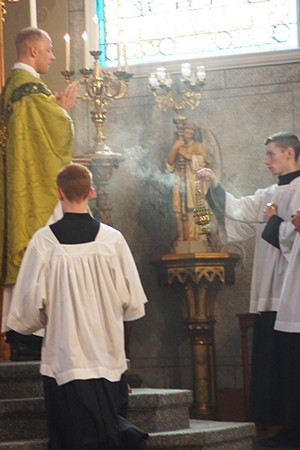 Altar boy Wyatt Clark, of Springfield, swings a thurible in Sacred Heart Catholic Church. The incense signifies prayers rising to God. - PHOTO BY SCOTT REEDER