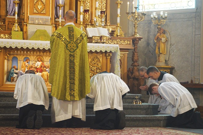 The Rev. Kevin Mann says the Confiteor prayer as the servers kneel at the beginning of the Latin Mass. - PHOTO BY SCOTT REEDER