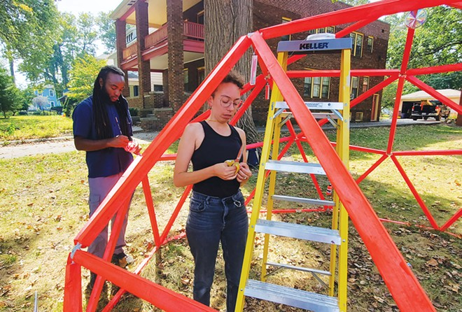 """Erin Washington hangs prisms from inside the dome – titled """"afterglow of radiation"""" – while Hasani Cannon assists by touching up the paint. - CREDIT: RACHEL OTWELL"""