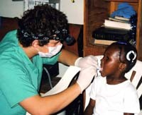 Josh Davis, a dental assistant, cleans the teeth of a Jamaican girl at a clinic in Joyland. Davis, an eighth-grader at Pleasant Plains, is the son of dentist Jim Davis.