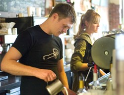 Andrew Tucker, left, and Barista Gabbrielle Hoover pouring drinks at One World Cafe in Moscow. - PHOTO MOSCOW-PULLMAN DAILY NEWS