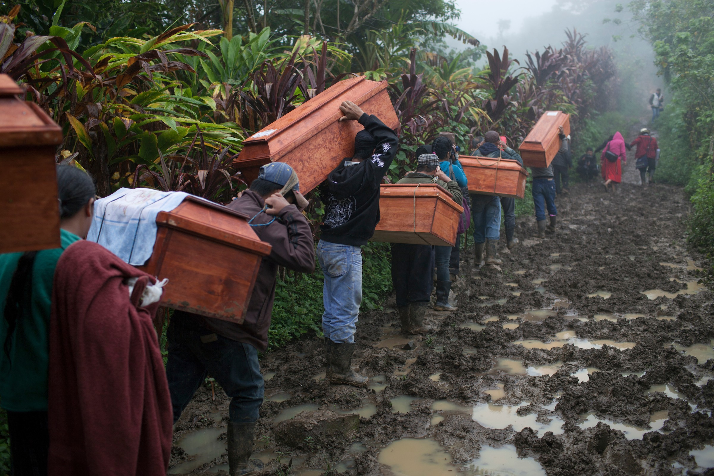 Community members from Estrella Polar and Covadonga hamlets head to the cemetery to bury the human remains of 77 war victims exhumed from mass graves in 2009. The victims were killed during the Covadonga massacre by the Guatemalan military forces on March 29, 1982, during the de facto government of General Efrain Rios Montt as part of a scorched earth campaign against numerous Mayan villages believed to support the guerrilla forces. Estrella Polar, Chajul, Quiché, Guatemala. November 20, 2014. - JAMES RODRIGUEZ / MIMUNDO.ORG