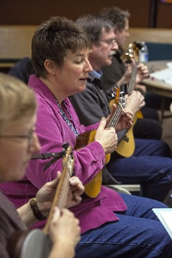 """Connie Stieger, left to right, Shelly Gilmore, Scott Hallett and Jim Kenyon play and sing """"Yellow Rose of Texas"""" with other Ukelele Players of the Palouse members during practice Thursday at Simpson United Methodist Church in Pullman. - DEAN HARE"""