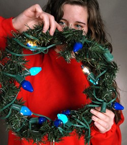 A lighted wreath makes for festive threads, but beware — it's better to leave the lights unplugged. During this photoshoot, one minute of powered lights around the neck resulted in smoking hair. - TRIBUNE/BARRY KOUGH