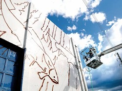 Artist Rolf Goetzinger washes off the winter dust and grime Monday on the west side of the Sonoco building as he prepares to finish his mural that will serve as the backdrop to the Canoe Wave sculpture near the Interstate Bridge in Lewiston. - KYLE MILLS, LEWISTON TRIBUNE