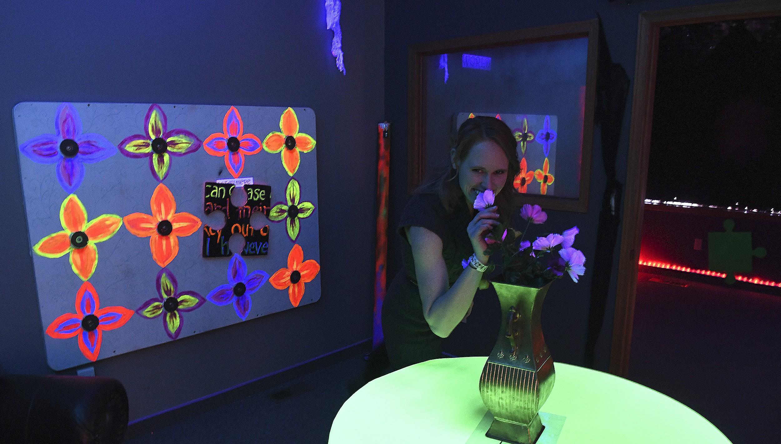 Kristen Legg sniffs the flowers in the Down the Rabbit Hole room. - TRIBUNE/STEVE HANKS