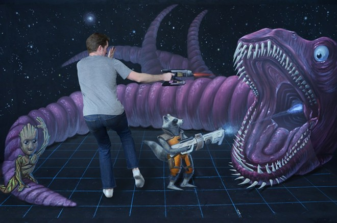 Chris Carlson poses in one of his works of chalk art which trick the eye with 3-D art.